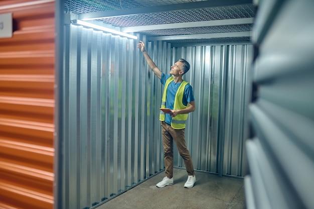 천장 근처에 매달려 램프를 확인하는 남자