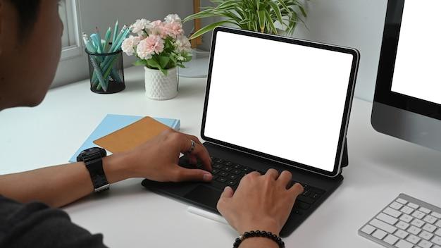 Человек, проверяющий почту на планшете в офисе.