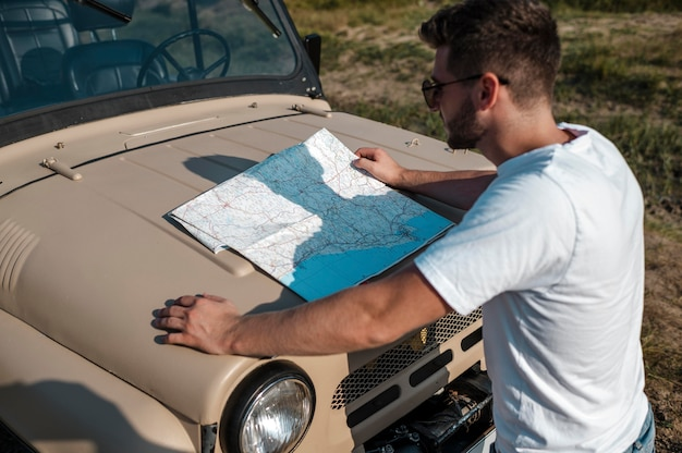 Человек проверяет карту во время путешествия в одиночку на машине