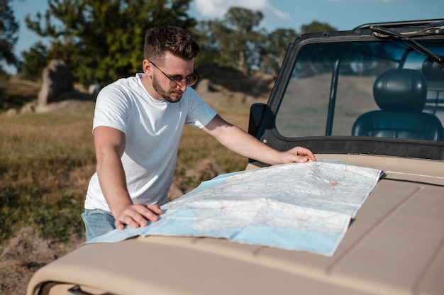 Man checking map while traveling by car