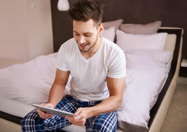 Человек проверяет утренние новости на своем планшете