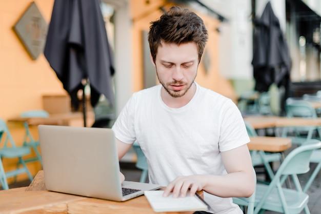 야외에서 집중하는 노트북 및 노트북을 확인하는 남자