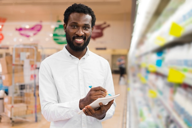 Man checking off items in shopping list
