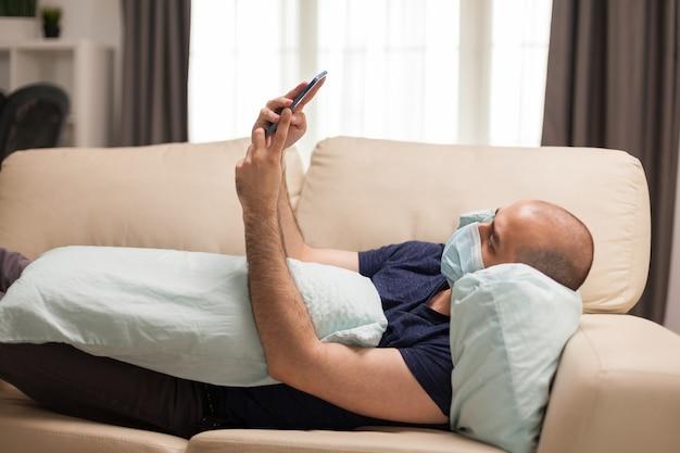 전 세계적으로 유행하는 동안 일회용 마스크를 쓰고 소파에 누워 스마트폰으로 소셜 미디어를 확인하는 남자.
