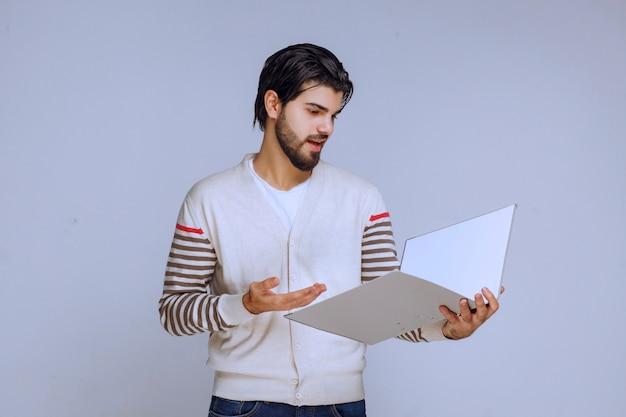 レポートフォルダをチェックし、そこに何が書かれているかを理解しようとしている男。 無料写真