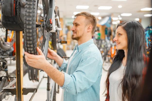 Человек проверяет поломку диска велосипеда, покупки