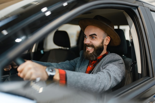 Man checks the interior of new pickup truck in car dealership. customer in vehicle showroom, male person buying transport, auto dealer business