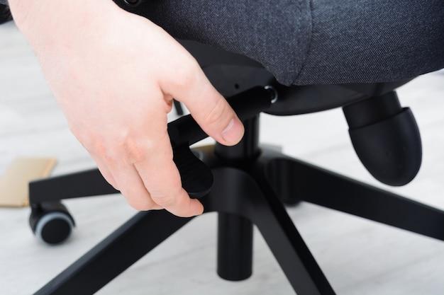 男は屋内でオフィスチェアを組み立てる椅子の持ち上げ機構をチェックします