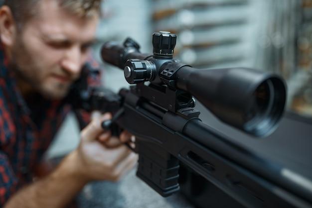 男は銃専門店で狙撃ライフルの照準器をチェックします