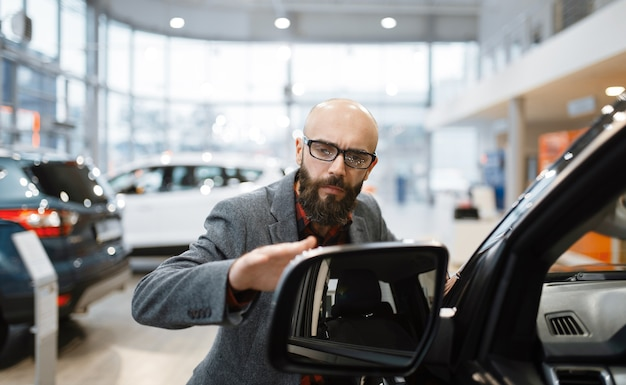 Man checks the paintwork of new pickup truck in car dealership.