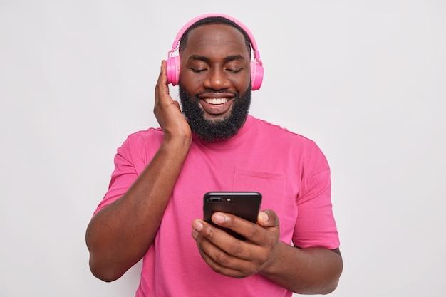 남자는 휴대전화를 들고 있는 새 헤드폰의 소리를 확인하고 흰색 다운로드 응용 프로그램에서 캐주얼한 분홍색 티셔츠를 입고 들을 노래를 선택합니다