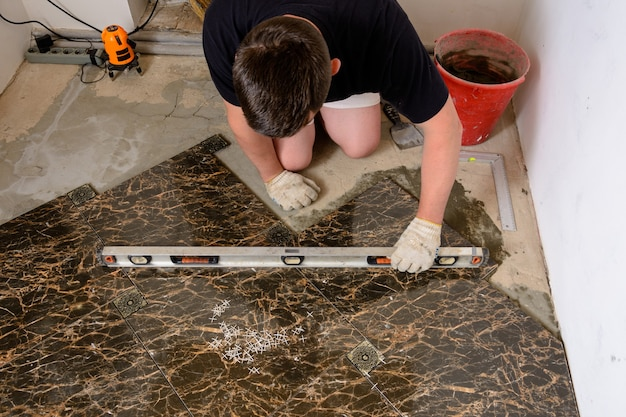 The man checks the surface of the tile using the level