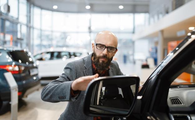 男は自動車販売店で新しいピックアップトラックの塗装をチェックします。