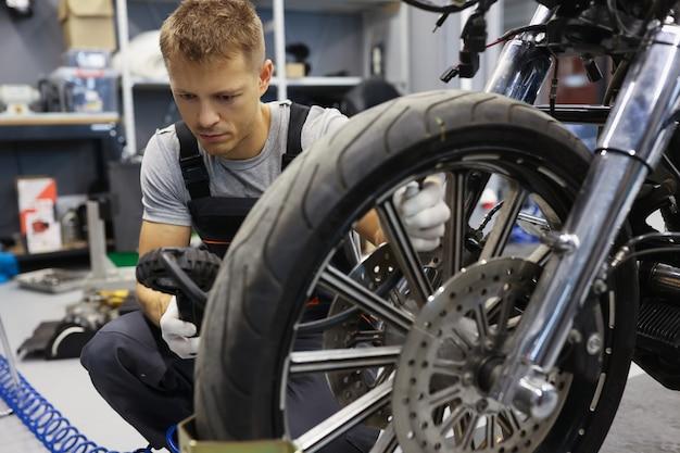 男はワークショップタイヤサービスコンセプトでオートバイのタイヤ空気圧をチェックします