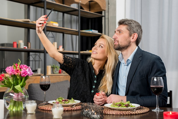 Man and cheerful woman taking selfie on smartphone at table