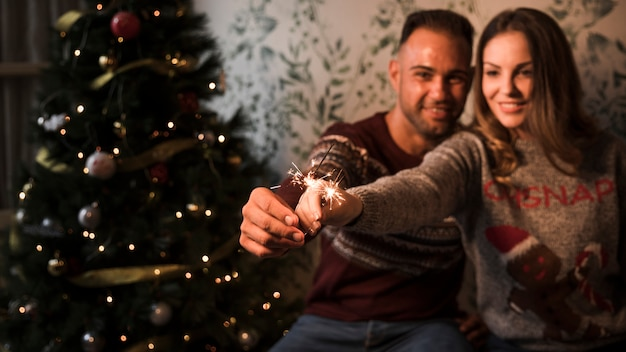 Man and cheerful woman with flaming bengal lights near christmas tree