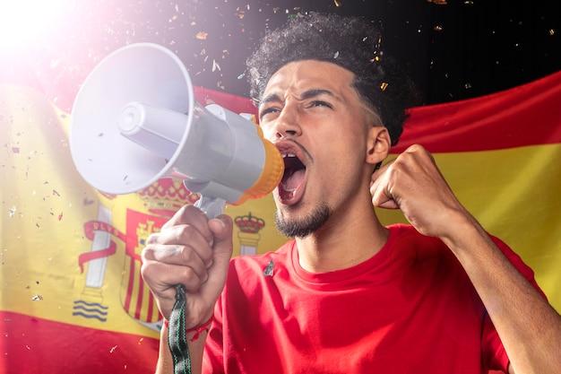 Человек аплодирует и говорит через мегафон с испанским флагом