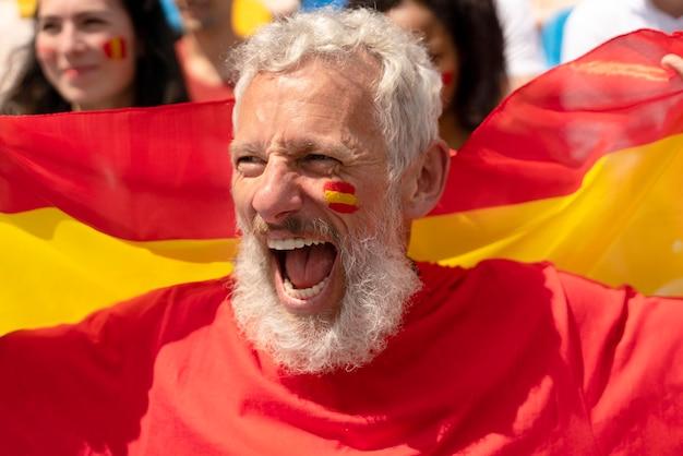 サッカーの試合に勝つ彼のチームを応援する男