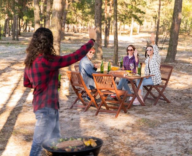 Uomo che esulta con gli amici mentre si tiene la birra e si mangia un barbecue