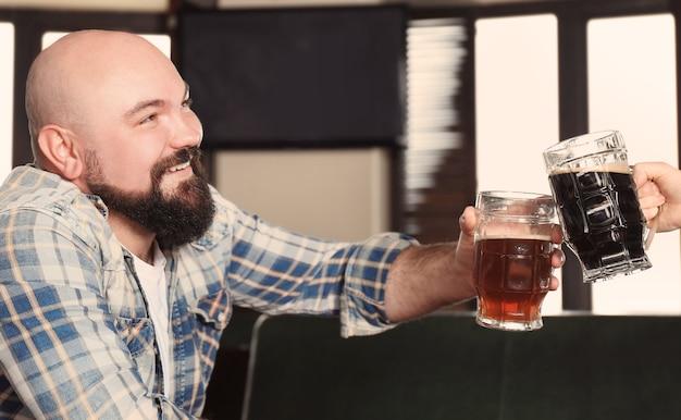 パブでビールのグラスで応援している男