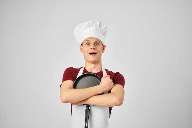 Человек шеф-повар обнимает сковородку, готовя светлый фон