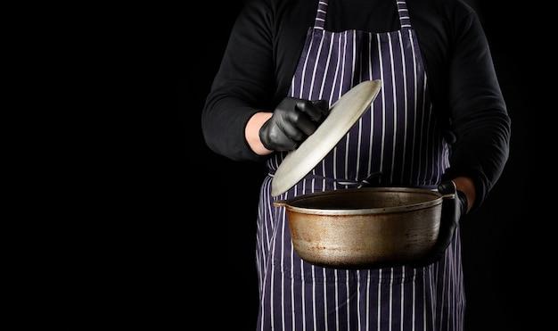 Мужчина повар в полосатом фартуке держит алюминиевый котел с крышкой, черный фон, пространство для копирования