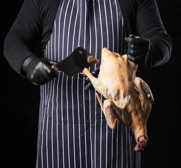Мужчина-повар в полосатом синем фартуке и черной одежде стоит на черном фоне и держит в руке утку для приготовления пищи
