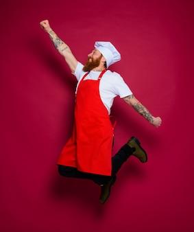 남자 요리사가 점프하고 슈퍼 영웅처럼 행동합니다.