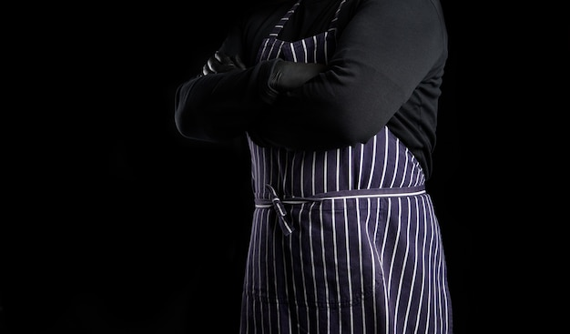 Man chef in a striped blue apron and black clothes stands against a black background, his arms are crossed on his chest, copy space