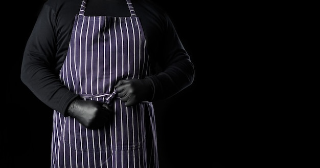 A man chef in a striped blue apron and black clothes stands on a black background, a place for an inscription