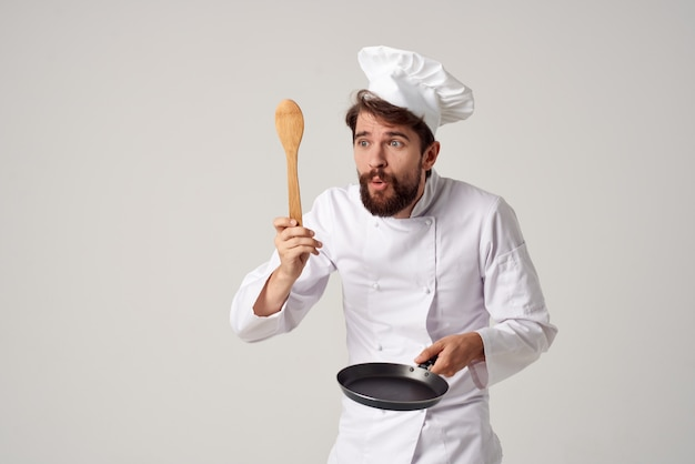 A man in a chefs uniform a frying pan in hands cooking work