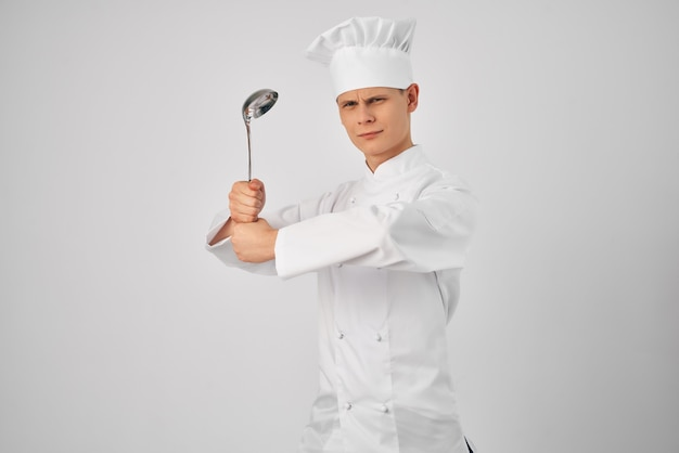 A man in a chefs uniform with a ladle in his hands preparing food light background