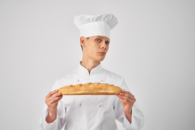 A man in a chefs uniform with a loaf in his hands fresh food work light background