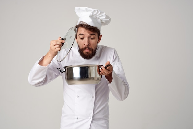 A man in a chefs uniform with a pan in his hands preparing food light background