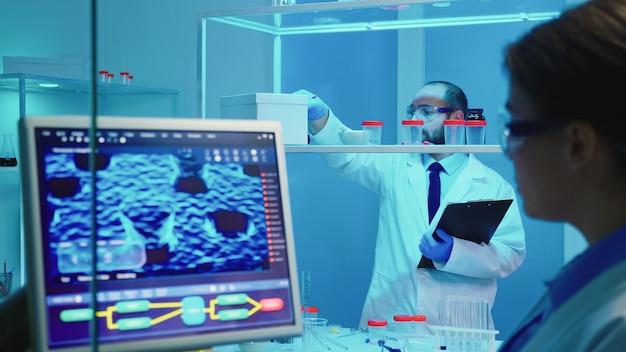 Chimico dell'uomo che controlla una bottiglia di pillole e strumenti di chimica che lavora fino a tardi per la ricerca medica