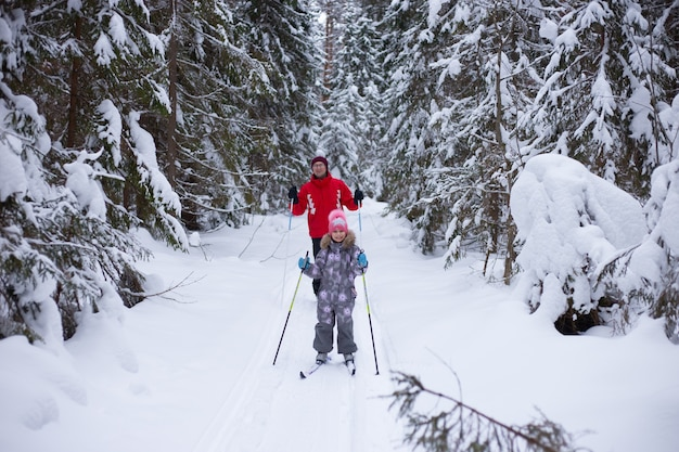 Man and child ski in winter in the forest