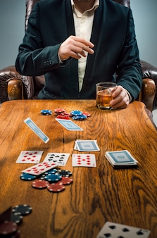 The man, chips for gamblings, drink and playing cards