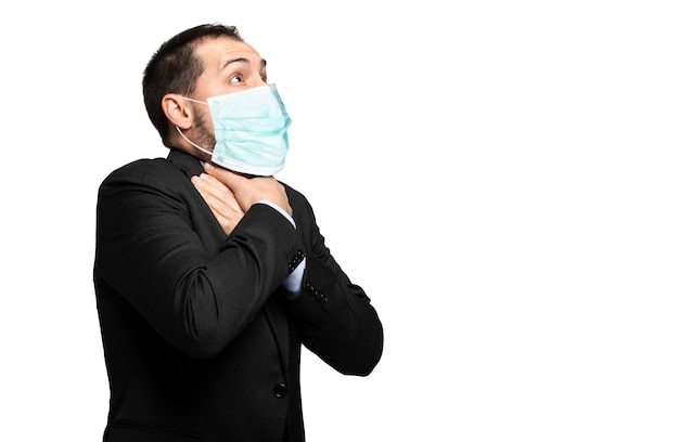 Man choking due to the lack of air isolated on white and wearing a mask, coronavirus concept