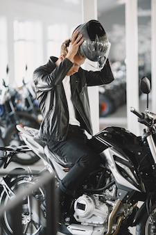 男はモトショップでバイクを選びました。黒のジャケットを着た男。ヘルメットをかぶった男。