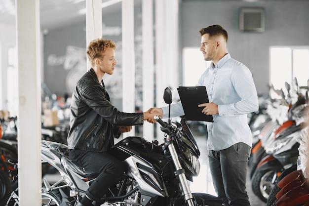 Мужчина выбирал мотоциклы в мото-магазине. парень в черной куртке. менеджер с клиентом.