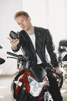 男はモトショップでバイクを選びました。黒のジャケットを着た男。
