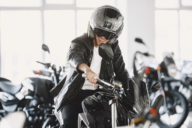 Man choosed motorcycles in moto shop. guy in a black jacket. man in a helmet.
