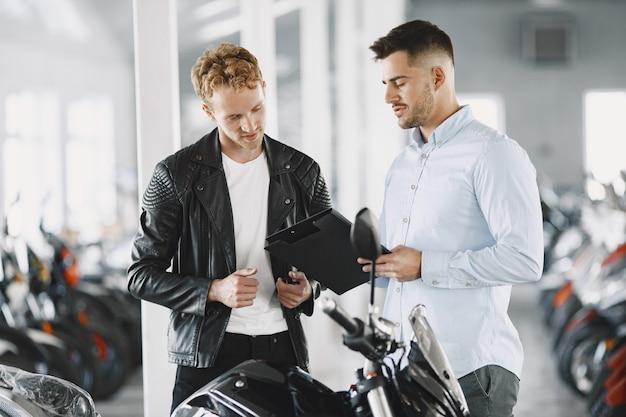 L'uomo ha scelto le motociclette nel negozio di moto. ragazzo con una giacca nera. manager con il cliente.