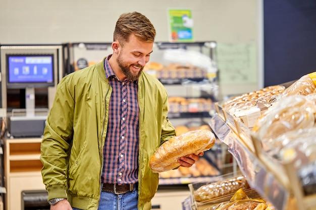 男はスーパーマーケットの食料品店で焼きたてのパンを選びます。男は店の農産物部門で食べ物を選ぶ