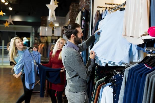 남자는 가게에서 셔츠를 선택합니다. 판매, 쇼핑, 패션, 스타일 및 사람들 개념