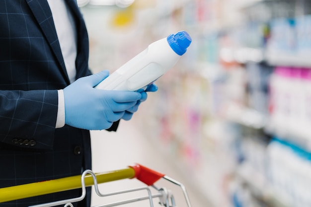 Man chooses detergent in household goods store, holds bottle with liquid powder, wears medical gloves to protect from coronavirus, reads product information. making shopping during quarantine