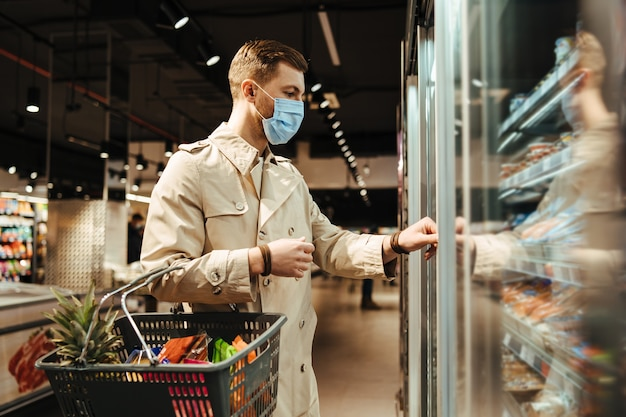 Man chooses goods from the refrigerator in the supermarket