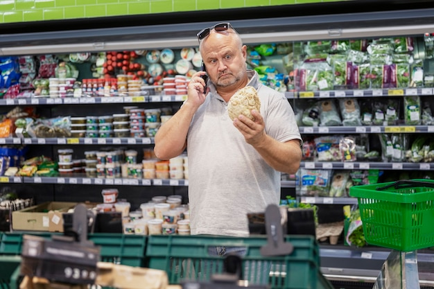 A man chooses vegetables in a supermarket. big choice. healthy eating and vegetarianism.