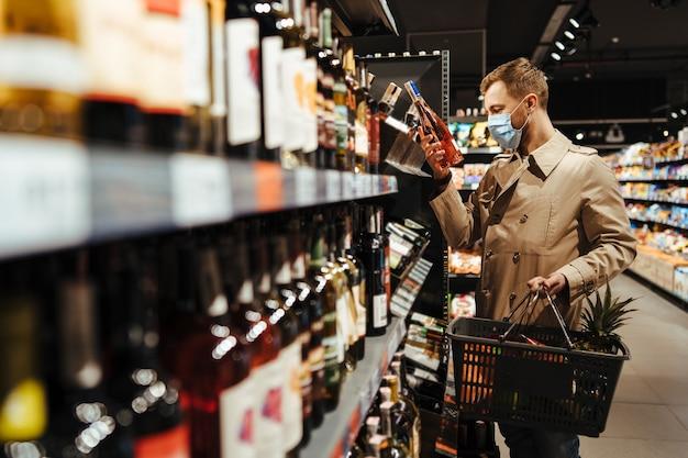 Мужчина выбирает вино в супермаркете