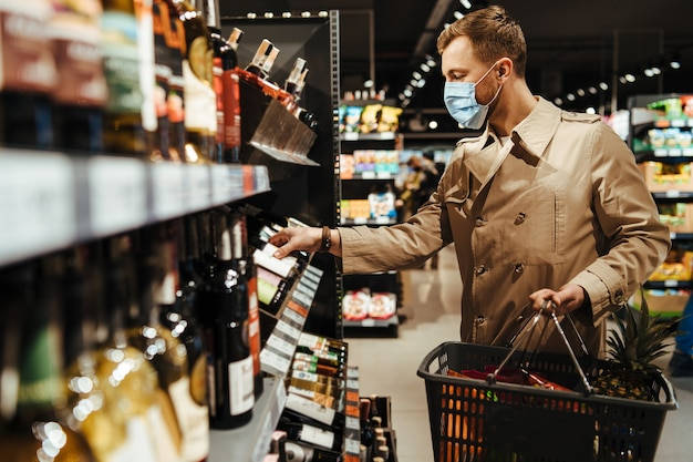 Man chooses wine in the supermarket